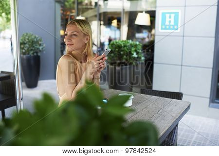 Hipster girl chatting on smart phone in sidewalk coffee shop terrace while enjoying a good day