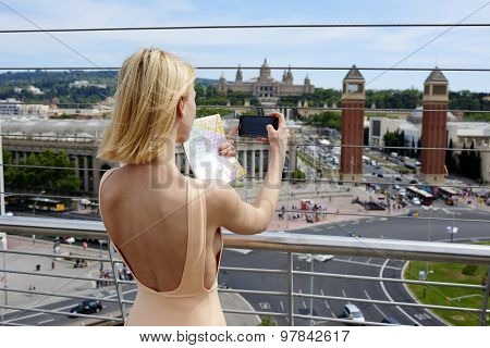 Back view attractive female tourist taking picture of active life in the city with her smartphone