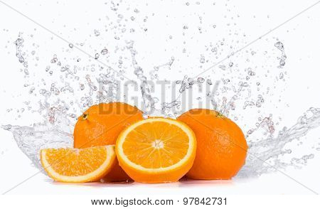 Fresh oranges with water splashes.