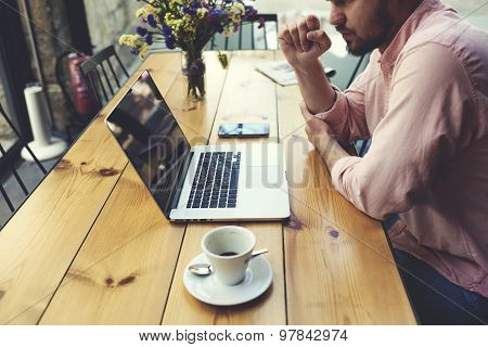 Thoughtful businessman work on notebook while sitting at wooden table in modern coffee shop interior
