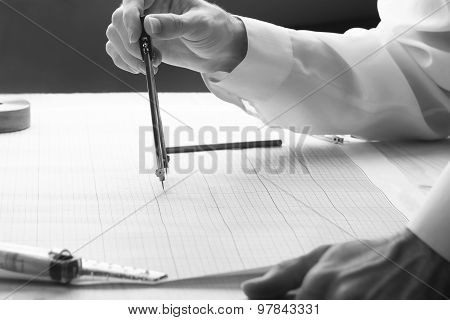 Man Examines Blueprint With A Divider