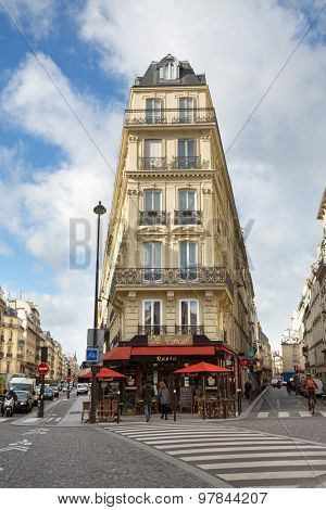 PARIS, FRANCE - MARCH 2, 2015: Busy street in central Paris, showing a street cafe and typical Parisian architecture.