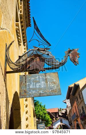 BARCELONA, SPAIN - MAY 02:Old rusty metal dragon shop sign with a sculpture of a wingerd dragon above a signboard mounted on an external wall.. May 02, 2015 in Barcelona Spain