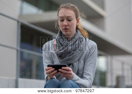 Thoughtful Woman Holding A Mobile Phone