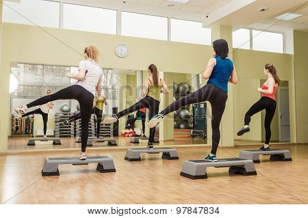 Group Of Women Making Step Aerobics From The Backside