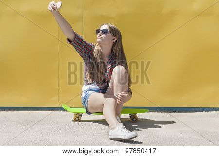 Stylish Young Girl Sitting On A Skateboard Makes A Self-portrait Smartphone.