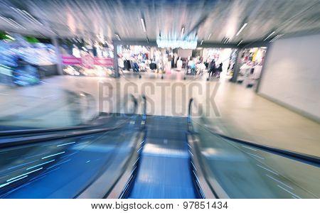 Shopping mall center escalators. Zoom blur movement.