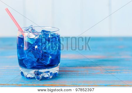 Blue alcohol or alcohol-free cocktail with straw and ice cubes on a wooden table. Empty space for te