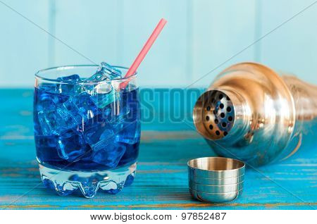 Blue alcohol or alcohol-free cocktail with straw, ice cubes and shaker on a light wooden background.