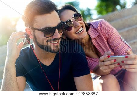 Two Friends Using Mobile Phone And Listening To Music In The Street.
