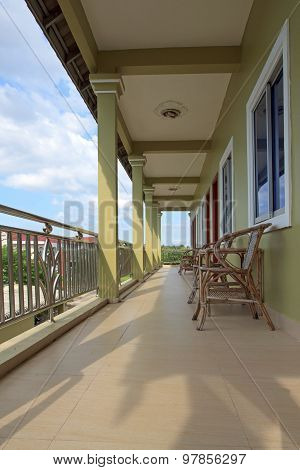 Motel Balcony With Wooden Chairs And Tables