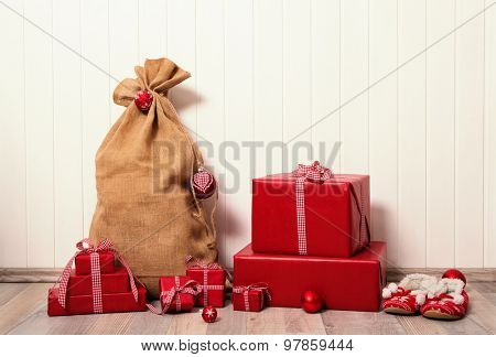 Classical christmas presents wrapped in red paper on white wooden background.
