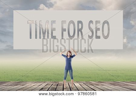 Time for SEO, words on blank board hold by a young girl in the outdoor.