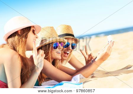 A picture of a group of friends taking selfie on the beach