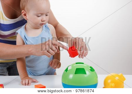 Baby And Mother Play With Toy In Blue Dress Smiling