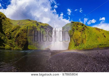 Iceland, waterfall Skogafoll summer, clouds of mist. Huge waterfall flowing from under a giant glacier