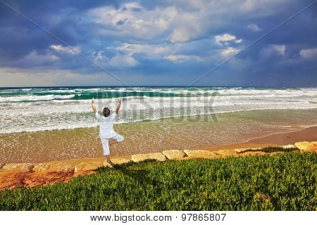 The beach in Tel Aviv. Storm cloud hanging over the sea, the woman in white performs asana