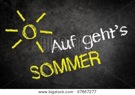 Conceptual Lets Go Summer (Auf gehts Sommer) Message in German Texts with Glowing Sun Drawing Written on a Black Chalkboard