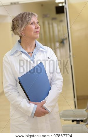 Senior doctor standing in hospital hallway watching outside