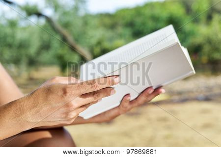 closeup of a young caucasian woman reading a book outdoors in a natural landscape in a sunny day