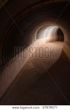 Dark concrete and metal curved tunnel with backlight