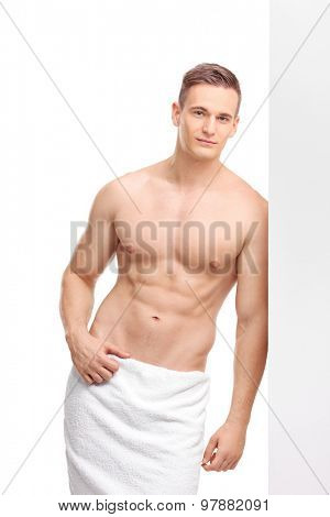 Vertical shot of a handsome young guy wearing nothing but a white bath towel around his waist leaning against a wall and looking at the camera isolated on white background
