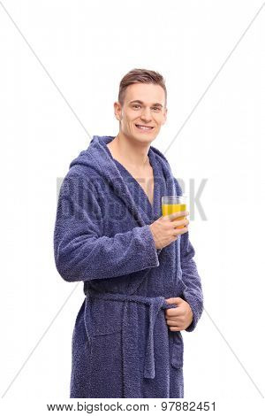 Vertical shot of a cheerful young man in a blue bathrobe holding an orange juice and looking at the camera isolated on white background