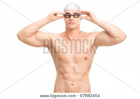 Studio shot of a young male swimmer with a gray swim cap and black swimming goggles isolated on white background