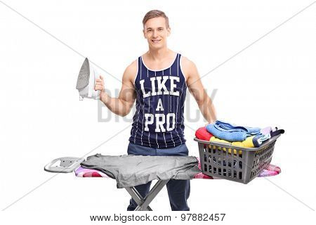 Young man standing behind an ironing board with an iron in his hand and looking at the camera isolated on white background