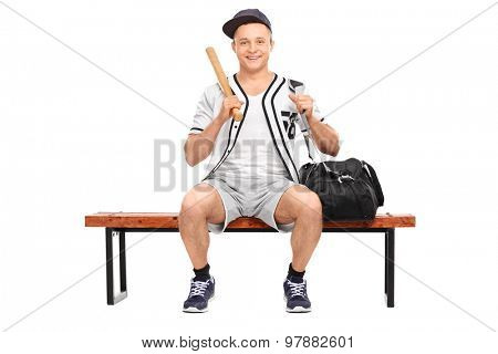 Young baseball player holding a baseball bat and sitting on a wooden bench isolated on white background
