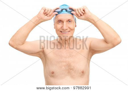 Cheerful senior with a blue swim cap putting on his swimming goggles and looking at the camera isolated on white background