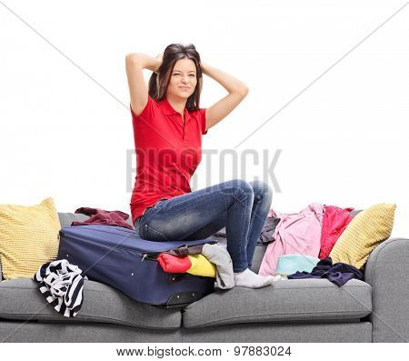 Upset young girl trying to pack all of her clothes in on suitcase isolated on white background