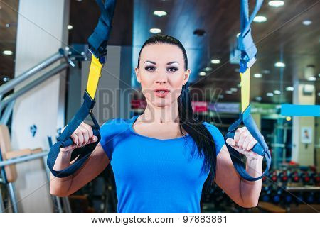 TRX. fitness, sports, exercise, technology and people concepts - smiling young woman doing exercise