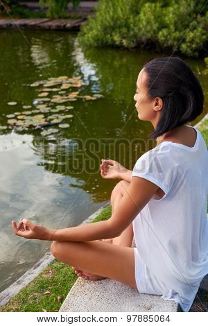 young female sitting near a pond, lake in a yoga position