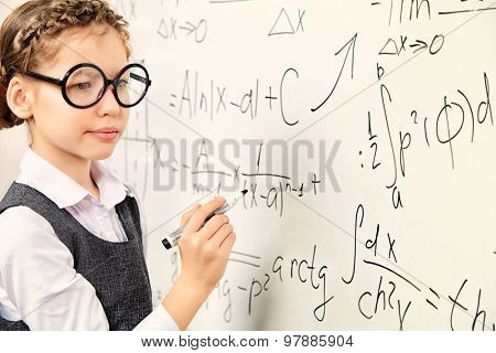 Happy smart schoolgirl in big glasses performs the task at the blackboard. Education.