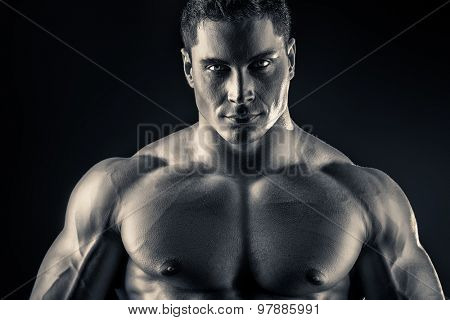 Handsome muscular bodybuilder posing over dark background. Glory of the champion.