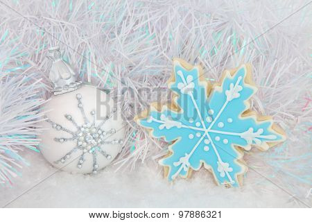 Christmas snowflake white bauble decoration and luxury gingerbread biscuit on snow with tinsel background.