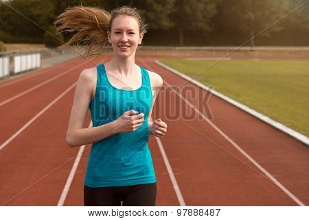 Young Woman Runner Training On A Track