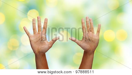 gesture, people and body parts concept - african woman two hands showing palms or making high five over green lights background