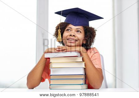 education, school, knowledge and people concept - happy smiling african american student girl in bachelor cap with books sitting at table and dreaming at home