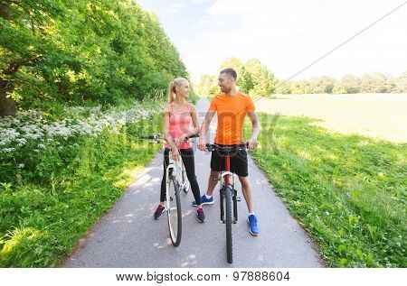 fitness, sport, people and healthy lifestyle concept - happy couple riding bicycle outdoors at summer