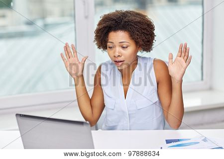 education, business, fail and technology concept - african american businesswoman or student with laptop computer and papers at office