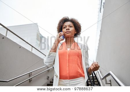 business, communication, technology and people concept - young african american businesswoman calling on smartphone going down stairs into city underpass