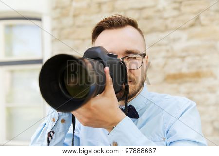 people, photography, technology, leisure and lifestyle - happy young hipster man holding digital camera with big lens taking picture on city street