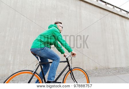 people, style, leisure and lifestyle - happy young hipster man riding fixed gear bike on city street