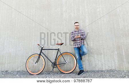 people, style, technology, leisure and lifestyle - happy young hipster man in earphones with smartphone and fixed gear bike listening to music on city street