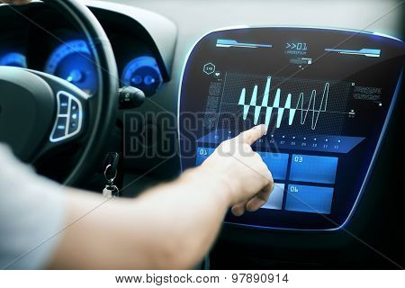 transport, modern technology and people concept - male hand pointing finger to diagram on screen of car control panel