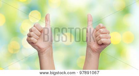 gesture, like, success, and people body parts concept - woman hands showing thumbs up over blue sky and clouds background