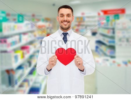 medicine, pharmacy, people, health care and pharmacology concept - happy male pharmacist holding red heart shape over drugstore background