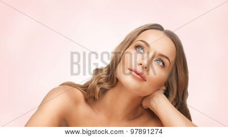 people, beauty and hair care concept - beautiful woman face with long blond hair r looking up and dreaming over pink background